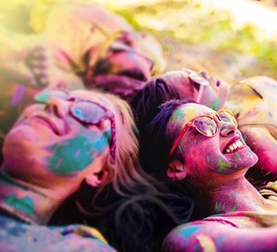 Teenager liegen bunt gefärbt am Boden