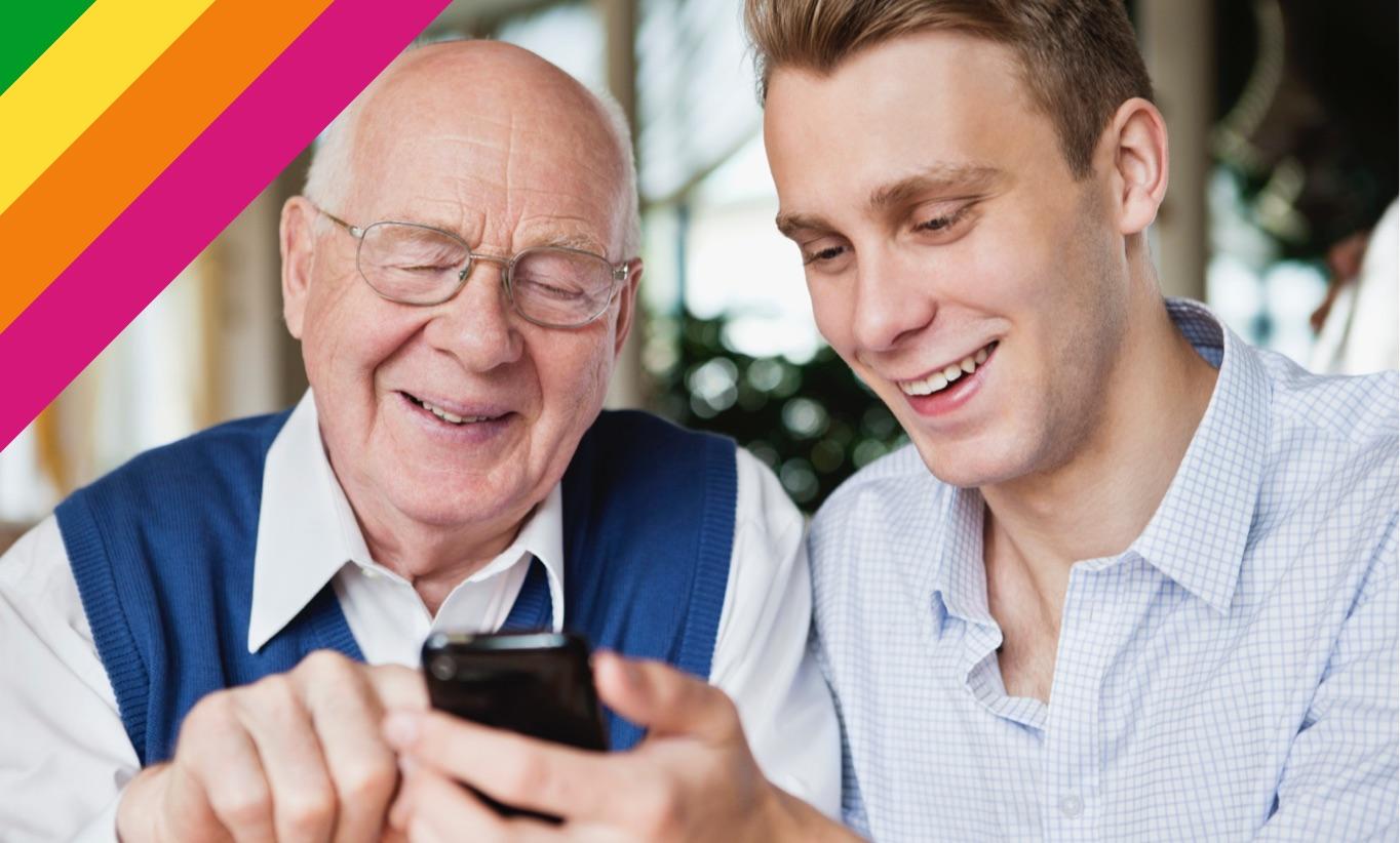 Opa und junger Mann schauen auf Smartphone