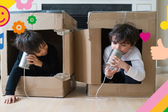 Zwei Kinder spielen in Kartons