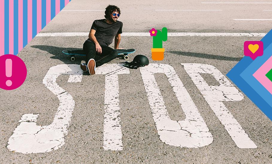Mann sitz mit Skateboard auf Straße mit bemaltem Stopzeichen