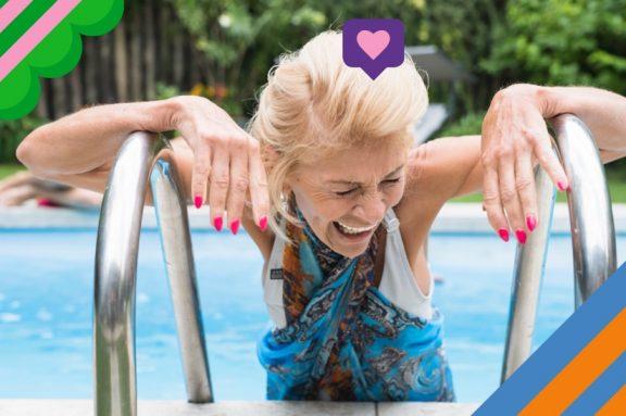 Ältere Dame stützt sich lachend am Pooltreppengeländer
