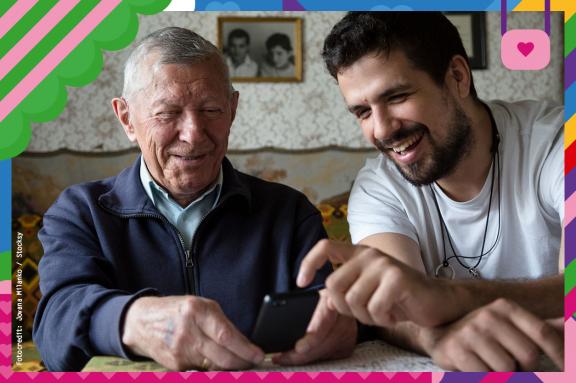 Mann zeigt älterem Herr was auf einem Handy