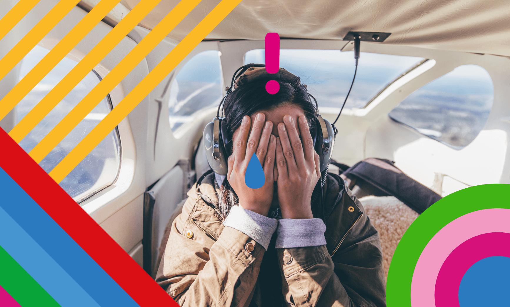 Frau versteckt Gesicht hinter Händen im Flugzeug