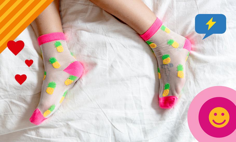 Füße mit bunten Socken im Bett