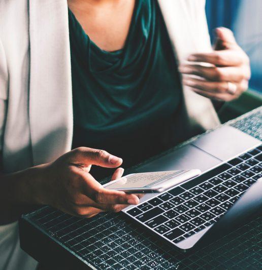 Frau am Laptop mit Handy in der Hand