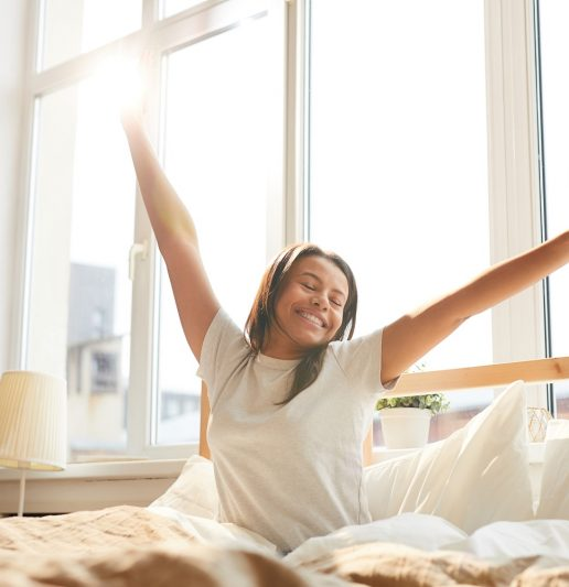 Frau streckt sich morgens im Bett