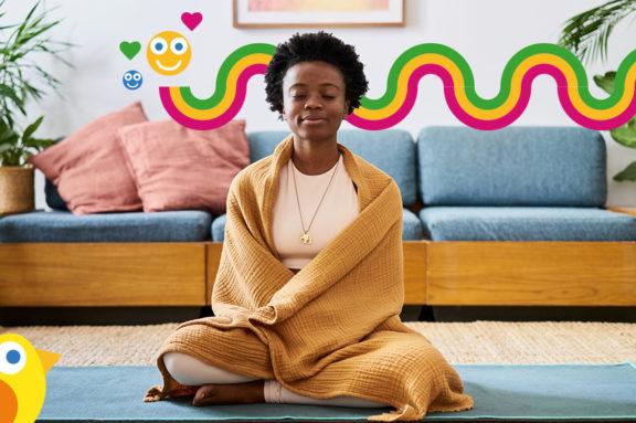 Eine Frau sitzt in Ihrem Wohnzimmer auf dem Boden und meditiert
