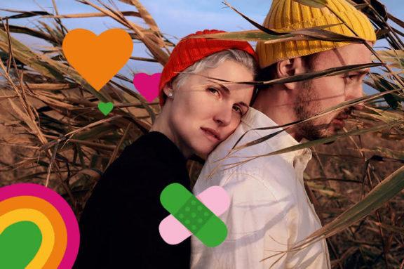 Ein junges Paar steht aneinander gelehnt im Feld