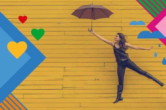 Frau fliegt mit einem Regenschirm vor einer gelben Wand