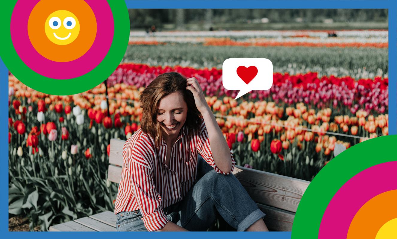 Eine Frau sitzt lächelnd auf Bank vor einem Tulpenbeet