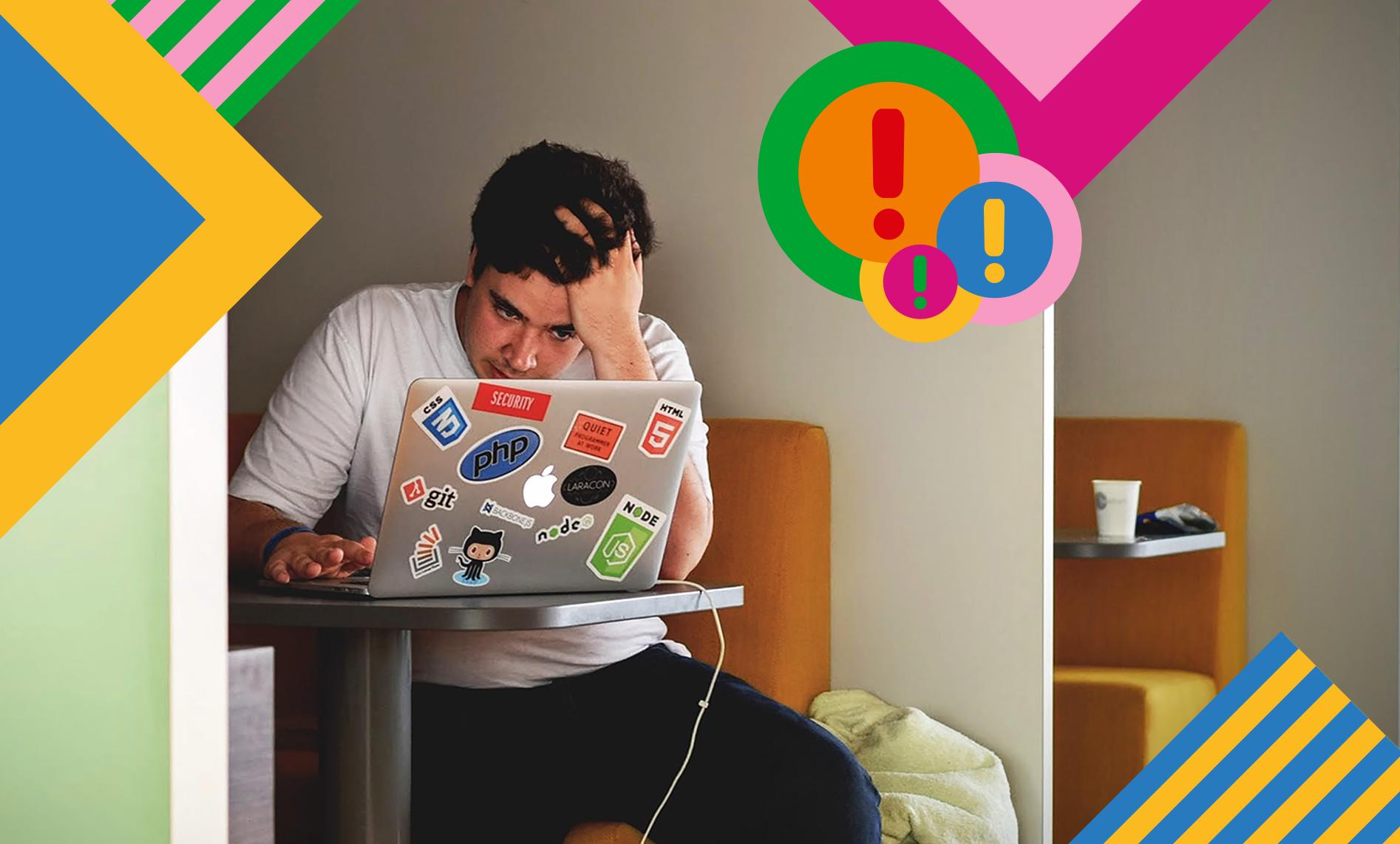 junger Mann rauft sich, am Computer sitzend, die Haare