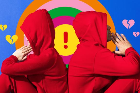 zwei Personen in roten Trainingsanzügen drehen sich sitzend den Rücken zu