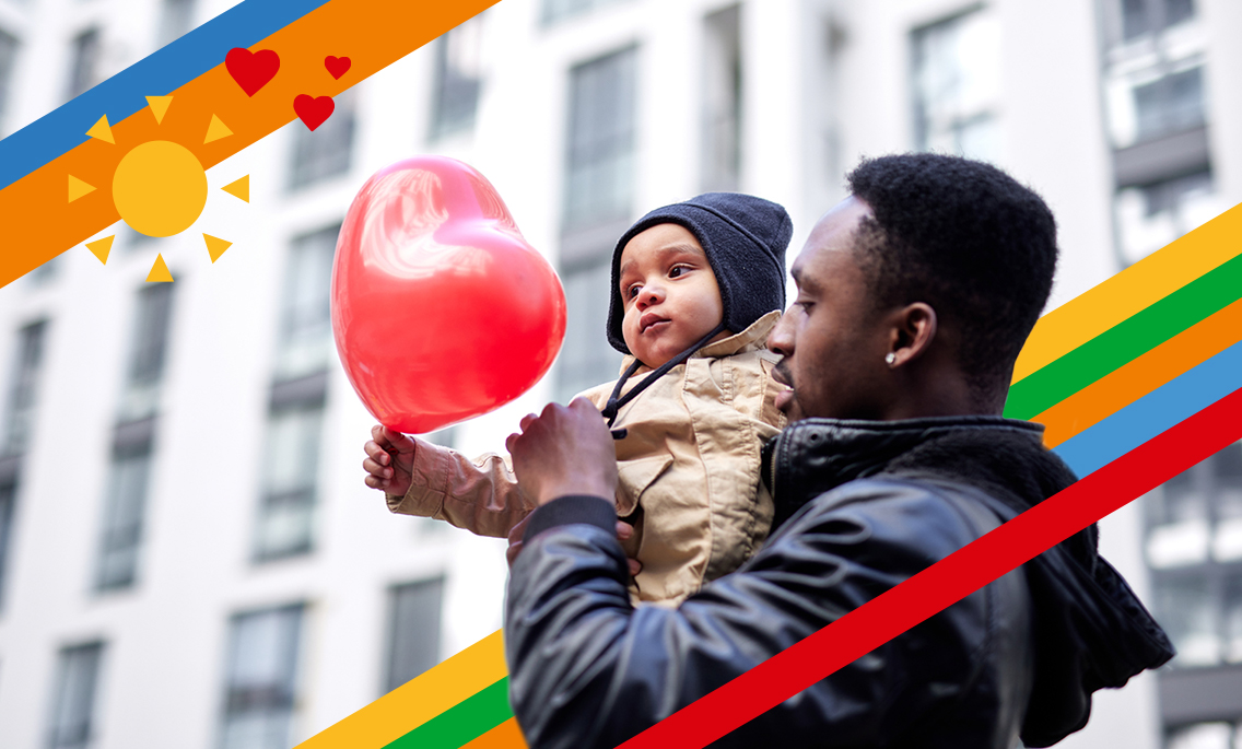 Vater trägt Kind mit Luftballon auf dem Arm
