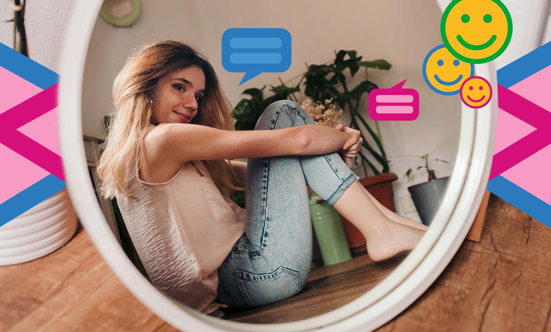 Frau sitzt lächelnd auf dem Boden vor einem Spiegel