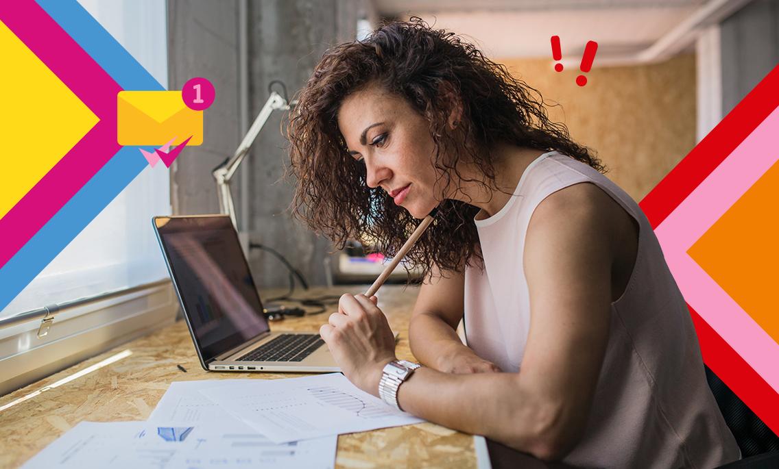 Eine Frau sitzt am Schreibtisch und liest Dokumente
